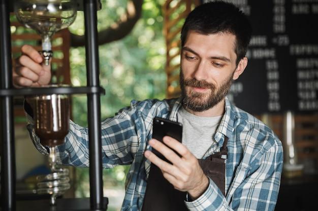 Immagine di un gioioso barista che indossa un grembiule che usa il cellulare e fa il caffè mentre lavora al bar o al caffè all'aperto