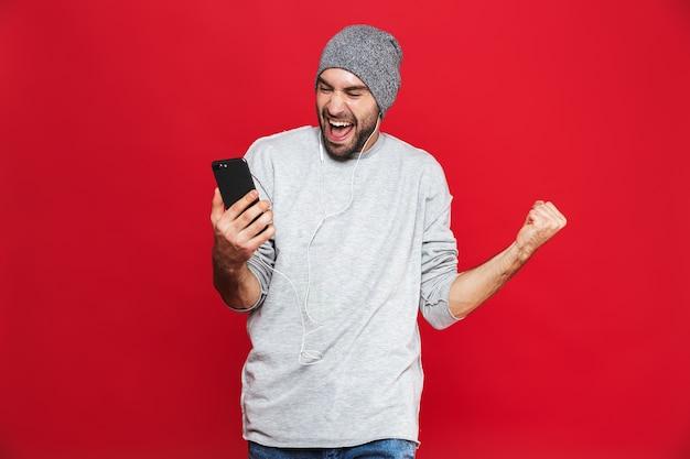 Immagine di uomo gioioso 30s ascoltando musica utilizzando auricolari e telefono cellulare, isolato