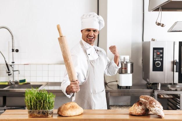 Immagine del fornaio uomo gioioso in uniforme bianca sorridente, mentre si trovava al forno con pane sul tavolo