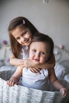 Immagine di bambini, fratello e sorella nel carrello sul prato