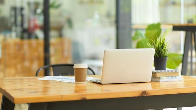 Immagine del supporto per computer portatile su un tavolo di legno con tazza di caffè, relazione, libri, pianta da interni nello spazio di co-lavoro della caffetteria