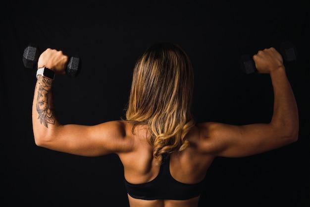 Immagine della schiena di una donna latina in forma con pesi su sfondo scuro.