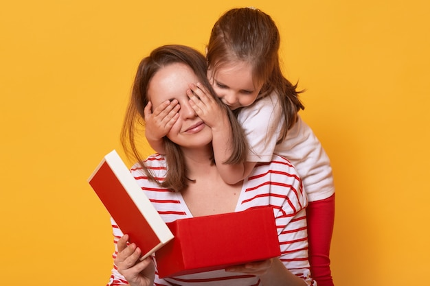 Immagine della piccola figlia carina chiudendo gli occhi della mamma
