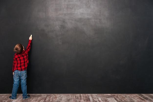 Immagine di un bambino carino in piedi vicino alla lavagna e che disegna su di esso