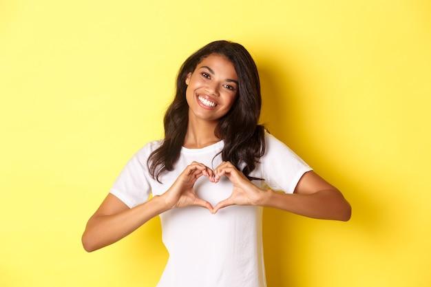 Immagine di una bella ragazza afroamericana in maglietta bianca che mostra il segno del cuore e sorride in piedi sopra di te...