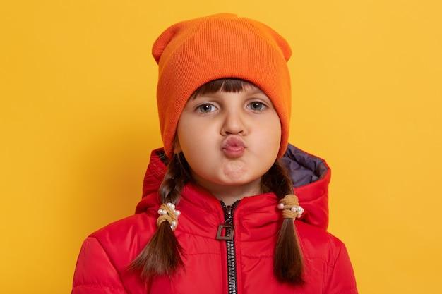 Immagine della graziosa ragazzina con labbra arrotondate che guarda con espressione sorpresa