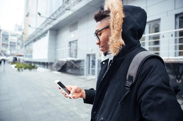 Immagine di un uomo che tiene il cellulare in mano e chiacchiera mentre ascolta la musica.