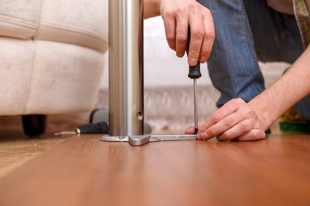Immagine dell'uomo che raccoglie mobili in camera