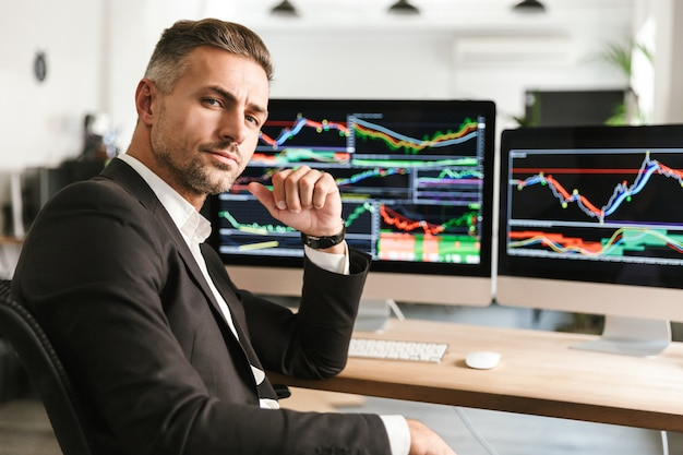 Immagine dell'uomo d'affari moderno 30s che indossa tuta lavorando in ufficio sul computer con grafici e grafici a schermo