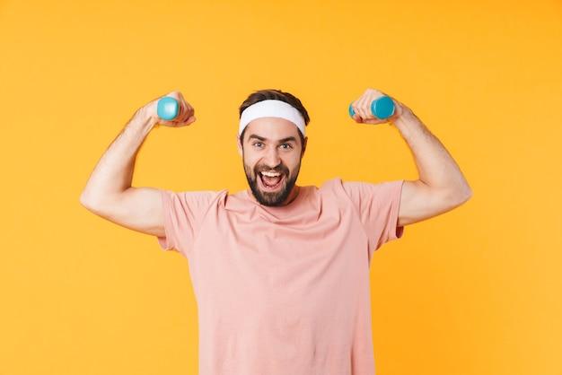 Immagine di un giovane atletico muscoloso in maglietta che si diverte e solleva manubri isolati su giallo