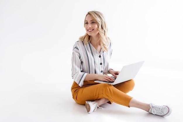 Immagine di bella donna sorridente che indossa abiti casual digitando sul laptop e guardando da parte mentre è seduto sul pavimento isolato sopra il muro bianco