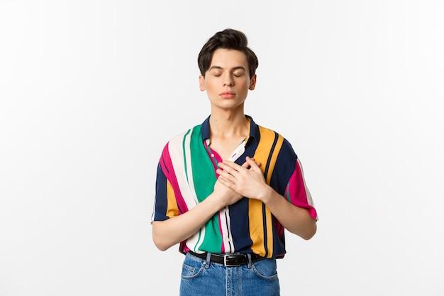 Immagine del giovane gay nostalgico in piedi con gli occhi chiusi e le mani sul cuore, ricorda qualcosa, in piedi sopra il bianco