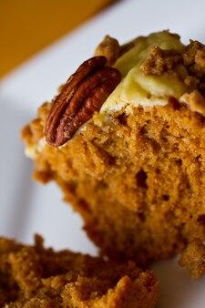 Immagine di muffin all'arancia con glassa e una guarnizione di noci pecan su un piatto bianco su uno sfondo arancione
