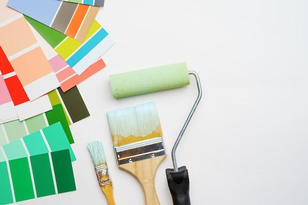 Immagine della tavolozza con colori blu e verdi, rullo, spazzole su sfondo bianco vuoto