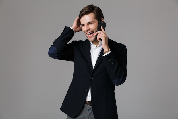 Immagine di uomo positivo 30s in tailleur parlando su smartphone nero, isolato sopra il muro grigio