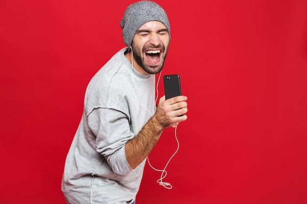 Immagine di un uomo positivo anni '30 che ascolta la musica utilizzando gli auricolari e il telefono cellulare, isolato