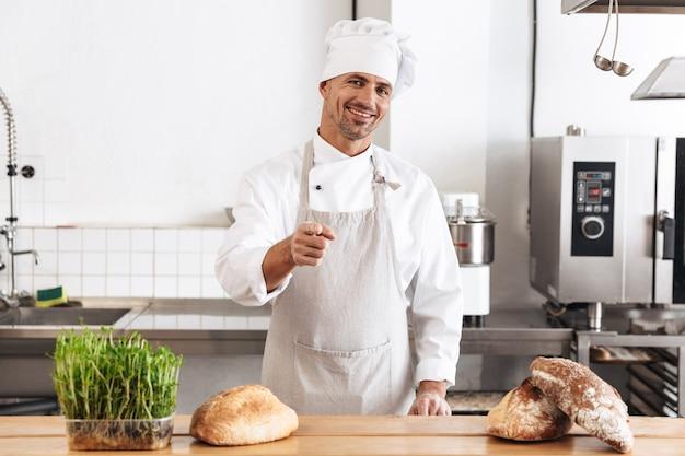 Immagine del fornaio uomo positivo in uniforme bianca sorridente, mentre si trovava al forno con pane sul tavolo