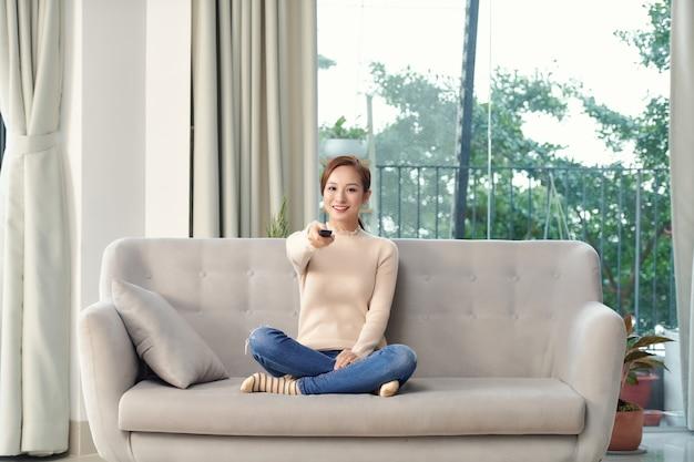 L'immagine di una giovane donna ottimista sorridente positiva si siede all'interno a casa guarda la tv tenendo il telecomando sul divano.
