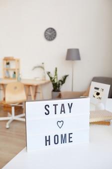 Immagine del poster con testo resta a casa nel soggiorno di casa