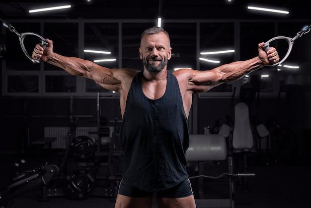 Immagine di un potente atleta che si esercita in un crossover in palestra. concetto di fitness e bodybuilding. tecnica mista