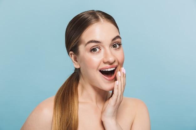Immagine di una giovane donna emozionante abbastanza felice che posa isolata sopra la parete blu.