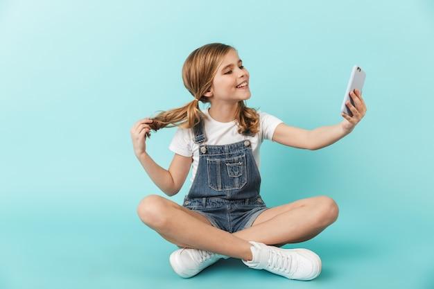 L'immagine di una giovane bambina abbastanza felice che posa isolata sopra il telefono cellulare wallusing blu prende un selfie.