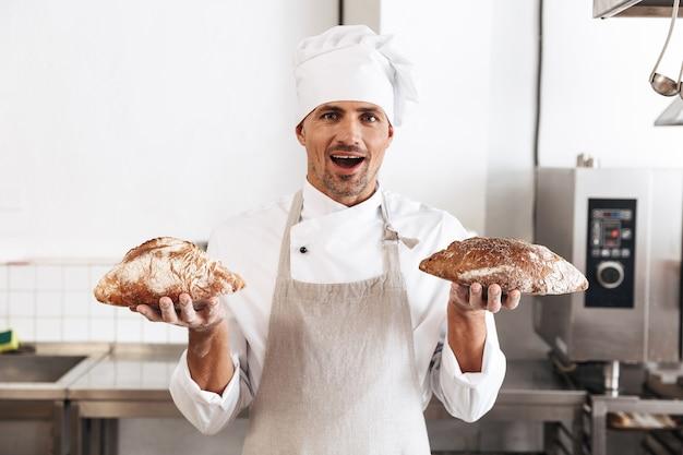 Immagine del panettiere maschio professionista in uniforme bianca in piedi al forno e tenendo il pane