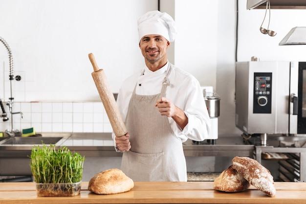 Immagine del panettiere uomo professionista in uniforme bianca sorridente, mentre si trovava al forno con pane sul tavolo