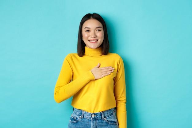 Immagine di una donna asiatica sorridente orgogliosa che tiene la mano sul cuore, mostrando rispetto per l'inno nazionale, in piedi su sfondo blu