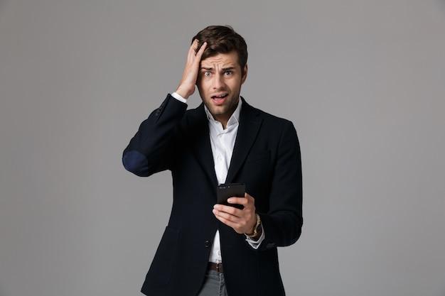 Immagine di uomo perplesso anni '30 in giacca e cravatta utilizzando smartphone nero, isolato sopra il muro grigio