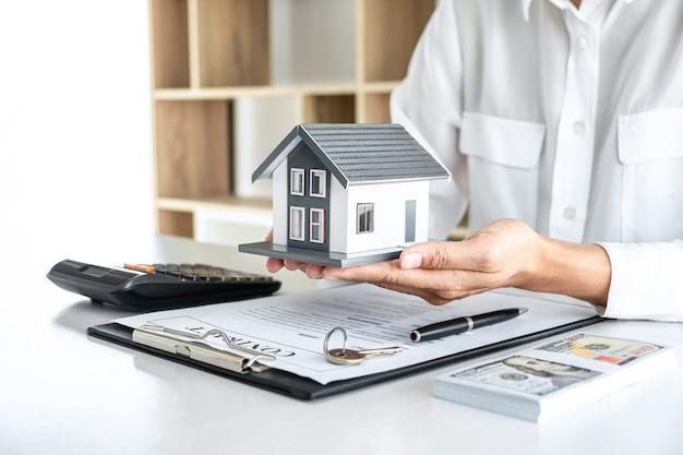 Immagine di un agente immobiliare che invia un modello di casa al cliente dopo l'approvazione, un'offerta di prestito ipotecario modello casa e un'assicurazione sulla casa.