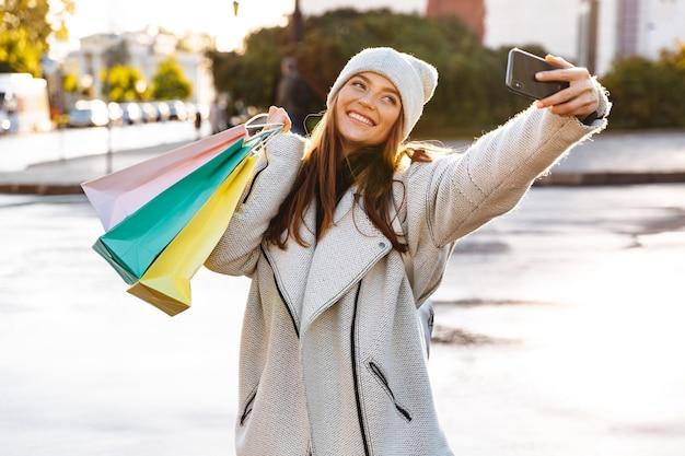 L'immagine di una donna felice rossa che cammina all'aperto tenendo le borse della spesa prende un selfie dal telefono cellulare.