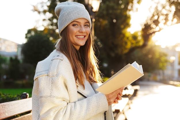 Immagine di una donna rossa seduta su una panchina all'aperto tenendo il libro di lettura.
