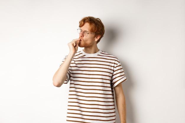 Immagine di un giovane soddisfatto con i capelli rossi e gli occhiali che baciano le dita, mostrando agli chef il gesto del bacio per lodare qualcosa di perfetto, in piedi su sfondo bianco