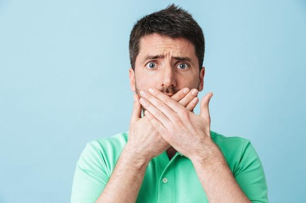 Immagine di giovane uomo barbuto bello confuso spaventato che posa isolato sopra la bocca blu del rivestimento murale.