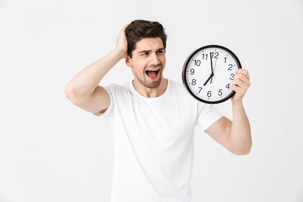 Immagine di urlare confuso giovane in posa isolato su muro bianco tenendo l'orologio.