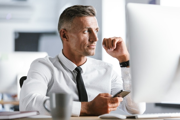 Immagine di uomo d'affari serio 30s indossa una camicia bianca e cravatta seduto alla scrivania in ufficio dal computer e tenendo lo smartphone