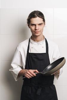 Immagine di uno chef cuoco giovane bello serio alla padella della holding della cucina.