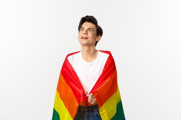 Immagine di una persona fluida di genere dall'aspetto serio con glitter sul viso, che indossa la bandiera arcobaleno lgbtq, in piedi sopra il bianco.