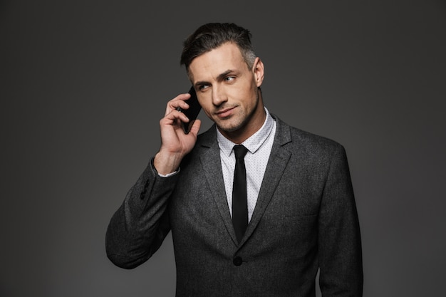 Immagine del datore di lavoro uomo serio vestito in costume di affari con parlare mobile in ufficio, isolato sopra il muro grigio