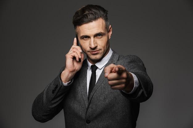 Immagine del datore di lavoro uomo serio vestito in costume di affari con parlare mobile in ufficio e puntare il dito su di te, isolato sopra il muro grigio