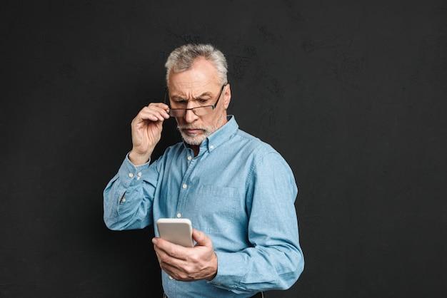 Immagine di grave uomo anziano maturo anni '60 con i capelli grigi alla ricerca sul cellulare con sguardo pensieroso durante la lettura o lo scorrimento di feed di notizie, isolato sul muro nero
