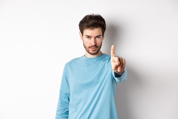 Immagine del giovane serio con la barba, agitando il dito in segno di disapprovazione, proibire o vietare qualcosa, in piedi su sfondo bianco e dire no Foto Premium
