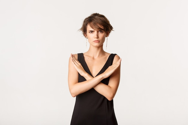 L'immagine di una giovane donna seria in abito elegante dice di fermarsi, facendo un gesto trasversale e accigliato arrabbiato, in piedi bianco.