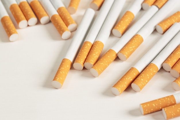 Immagine di parecchie sigarette di mucchio commercialmente fatte su sfondo bianco. o concetto di campagna per non fumatori, vista dall'alto del modello di tabacco.