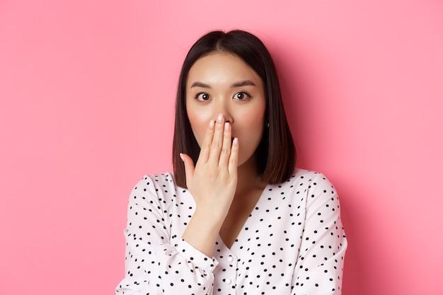 Immagine di una ragazza asiatica scioccata che spettegola, ansima e copre la bocca, fissa la telecamera con completa incredulità, in piedi su sfondo rosa