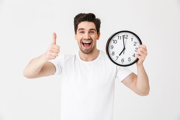 Immagine del giovane felice emozionante colpito che posa isolato sopra l'orologio bianco della tenuta della parete che mostra i pollici in su.