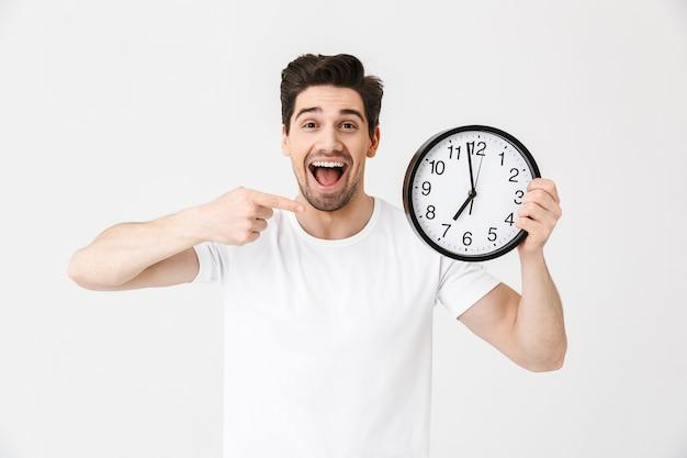 Immagine del giovane felice emozionante colpito che posa isolato sopra l'orologio bianco della tenuta della parete.