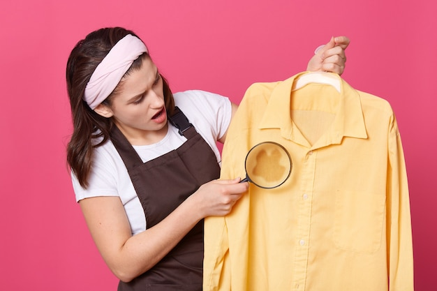 L'immagine della governante scioccata tiene in mano la camicia gialla e la lente d'ingrandimento, guarda con stupore il grande punto sporco, in posa con la bocca aperta contro il muro rosa.