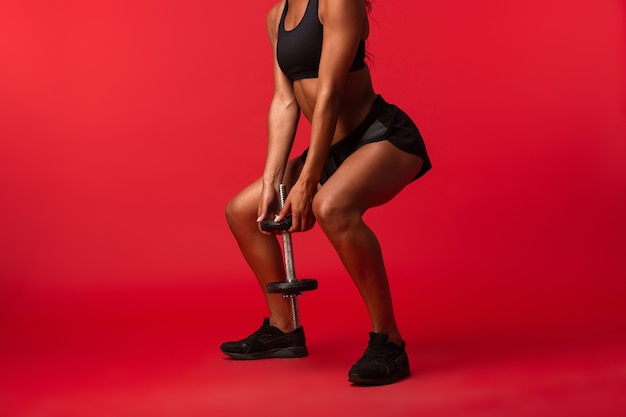 Immagine della donna afroamericana magra in abiti sportivi neri che solleva il manubrio, isolato sopra la parete rossa